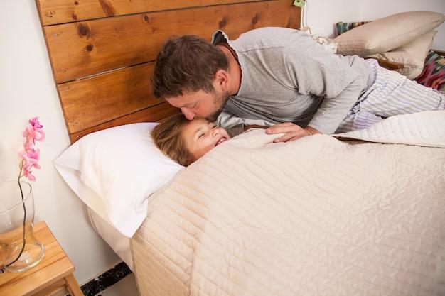 Vater küsst die stirn seiner tochter, bevor er schläft