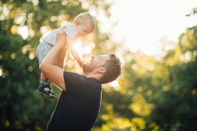 Vater lächelt seinen sohn von der seite an