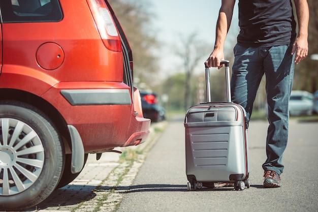 Vater lädt ein gepäck zum auto, bereitet sich auf einen urlaub oder urlaub im ausland vor, transportkonzept