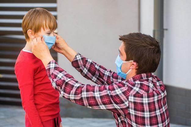 Vater legt ihrem sohn eine medizinische maske auf. coronavirus.