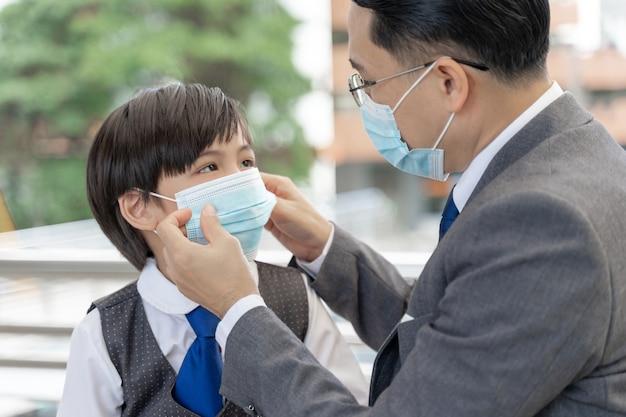 Vater legt seinem sohn eine schutzmaske auf, asiatische familie trägt eine gesichtsmaske zum schutz während des ausbruchs des coronavirus-covid-19-quarantänes
