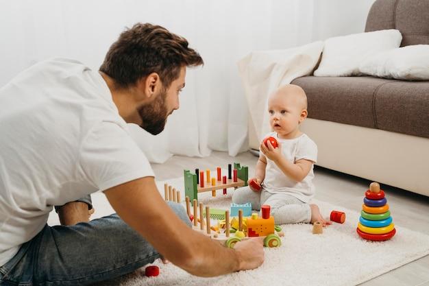 Vater lehrt baby, mit spielzeug zu spielen