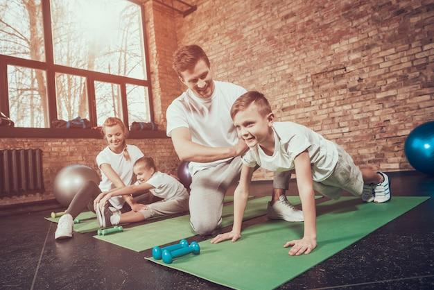 Vater lehrt sohn, sohn im fitnessstudio hochzudrücken.