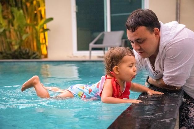 Vater lehrt süßes kleinkind kleines mädchen im badeanzug, im pool zu schwimmen und seine hand zu halten.