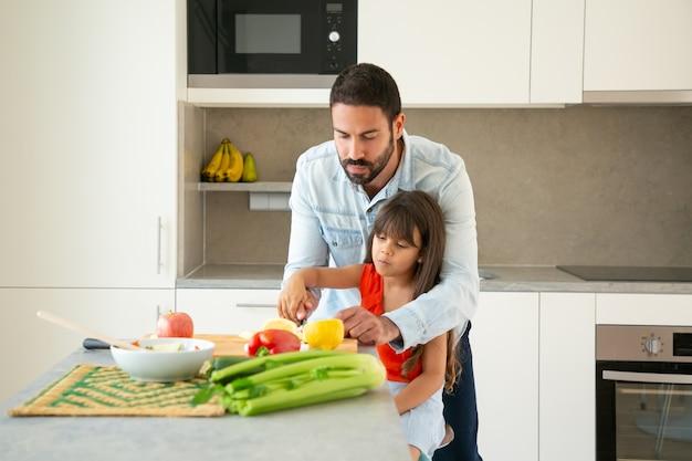 Vater lehrt tochter, salat vorzubereiten. mädchen und ihr vater schneiden frisches gemüse an der küchentheke. familienkochkonzept