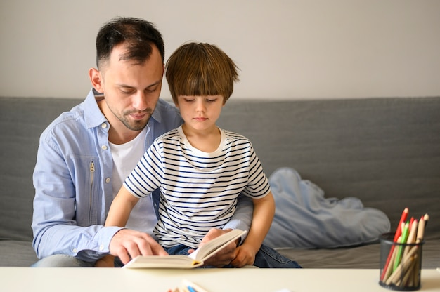 Vater liest dem sohn ein buch vor