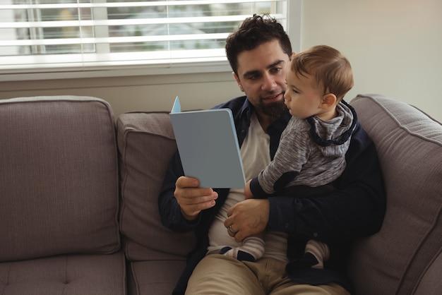 Vater liest ein buch, während er sein baby hält