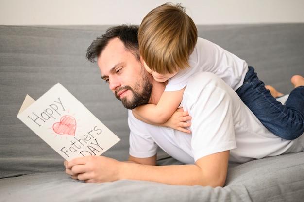 Vater liest grußkarte auf der couch