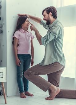 Vater misst seine tochter größe an der wand im kinderzimmer.