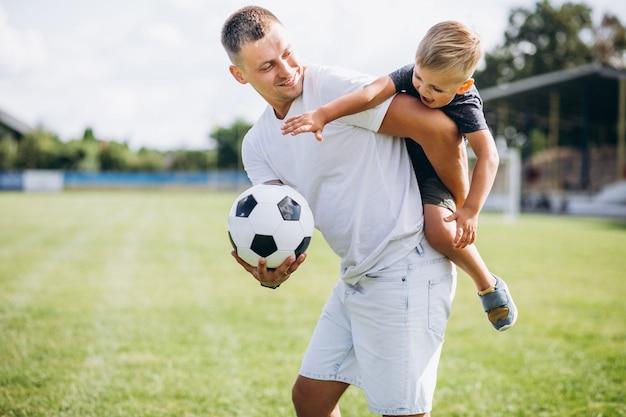 Vater mit dem sohn, der fußball am feld spielt