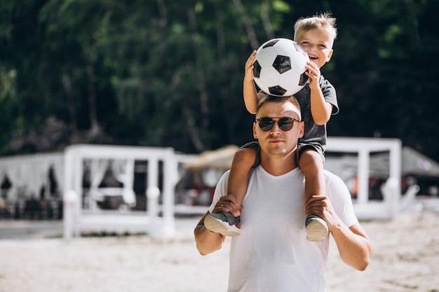 Vater mit dem sohn, der fußball am strand spielt
