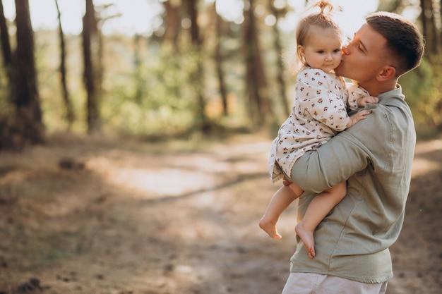 Vater mit der kleinen tochter, die im wald umarmt