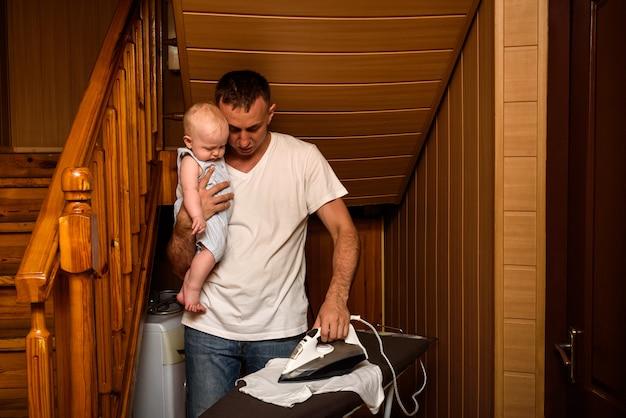 Vater mit einem kleinen baby in den armen bügelte leinen. hausarbeit machen