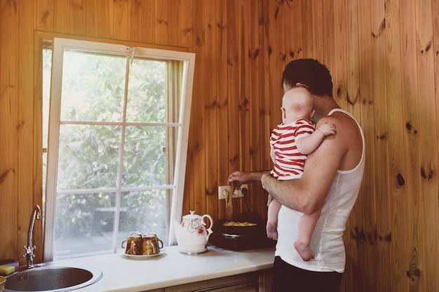 Vater mit einem kleinen baby in seinen armen kocht abendessen