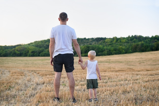 Vater mit einem kleinen sohn stehen auf einem gemähten weizenfeld.