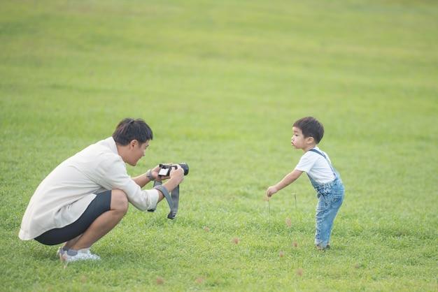 Vater mit einer digitalen videokamera, die seinen sohn aufzeichnet. porträt des glücklichen vaters und des sohns im park.