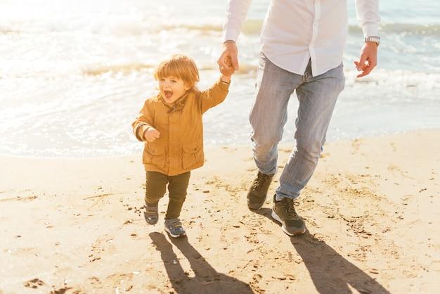 Vater mit glücklichem sohn am strand