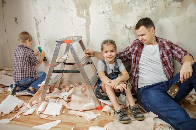 Vater mit kind, das raum zusammen repariert und tapete zusammen hängt