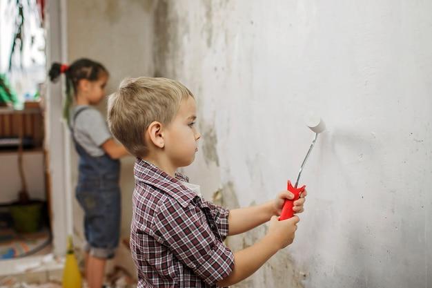 Vater mit kind repariert zimmer zusammen und malt die wand zusammen