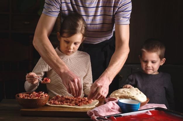 Vater mit kindern bereiten ein dessert vor