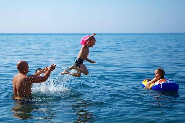 Vater mit kindern, die im meer schwimmen, das konzept eines familienurlaubs.