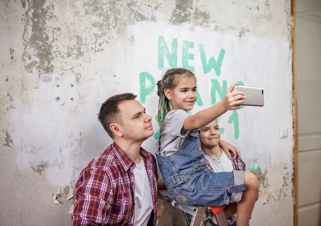 Vater mit kindern, die neues jahr mit checkliste an der wand planen und selfie mit smartphone machen