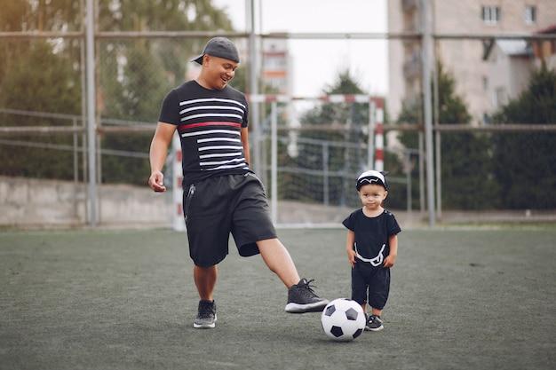 Vater mit kleinem sohn, der fußball spielt