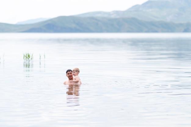 Vater mit kleinem sohn im meer schwimmen,