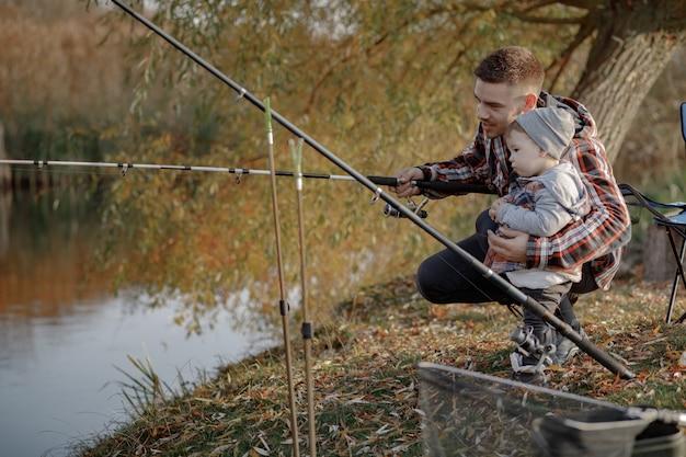 Vater mit kleinem sohn in der nähe des flusses an einem fischermorgen