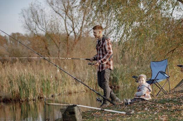 Vater mit kleinem sohn in der nähe des flusses an einem morgen beim angeln