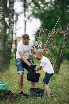 Vater mit kleinem sohn pflanzen einen baum auf einem yard