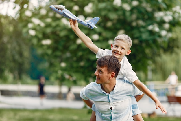 Vater mit kleinem sohn spielt mit spielzeugflugzeug