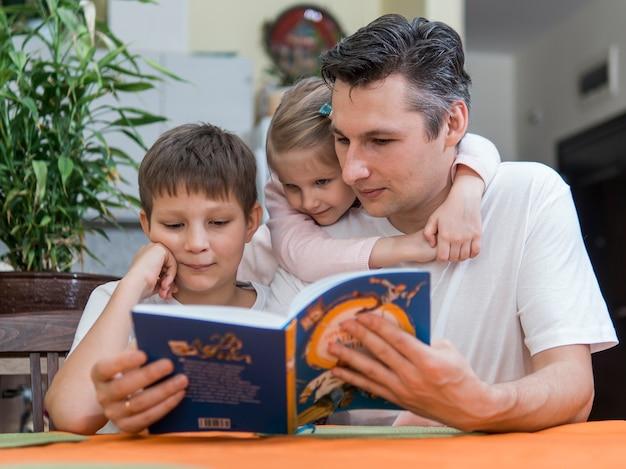 Vater mit mühe und schwesterkindern, die ein buch lesen