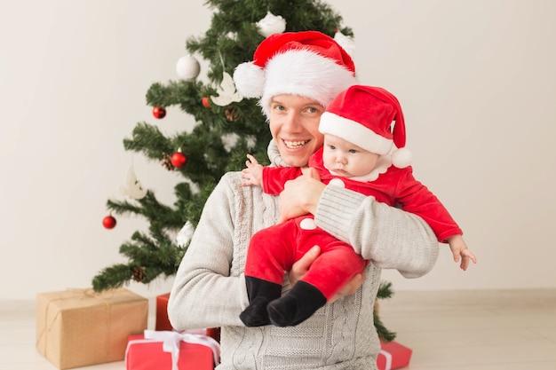 Vater mit seinem baby, das weihnachtsmützen trägt, die weihnachten feiern