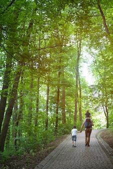 Vater mit seinen söhnen geht in den park. mit der familie durch den wald spazieren. rückansicht vertikaler rahmen