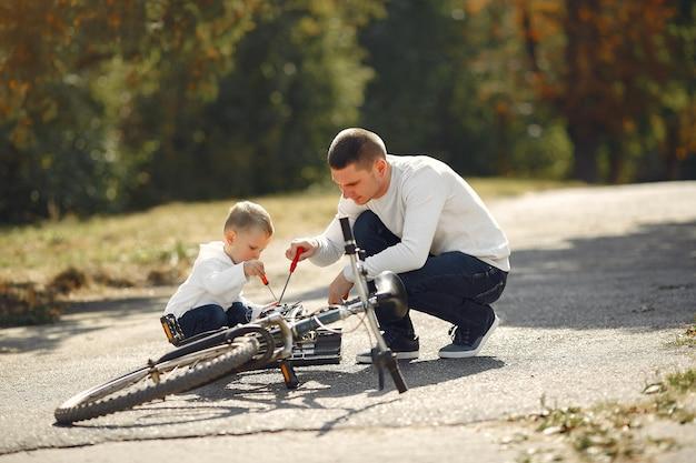 Vater mit sohn reparieren das fahrrad in einem park