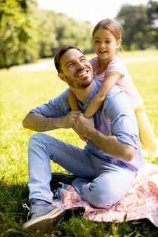 Vater mit süßer kleiner tochter, die spaß auf dem gras im park hat
