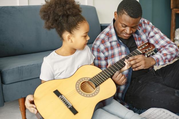 Vater mit tochter auf der couch. mädchen, das eine gitarre hält. gitarre lernen.