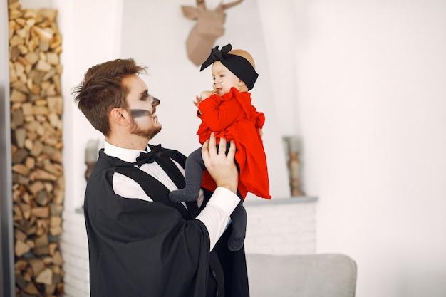 Vater mit tochter in kostümen und make-up. familie bereiten sich auf die feier von halloween vor.