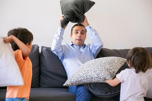 Vater mittleren alters spielt mit kindern und kämpft mit kissen. liebender kaukasischer vater, der auf sofa sitzt und spaß mit zwei verspielten söhnen zu hause hat. konzept für kindheit, wochenende und spielaktivität