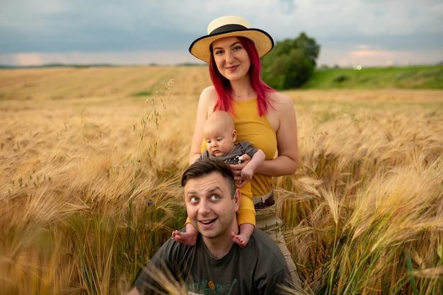 Vater, mutter und ihr kleiner sohn haben gemeinsam spaß auf einem weizenfeld.