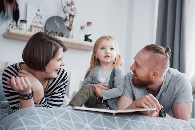 Vater, mutter und kleine tochter, die das buch der kinder auf einem sofa im wohnzimmer lesen. glückliche große familie las ein interessantes buch an einem festlichen tag. eltern lieben ihre kinder