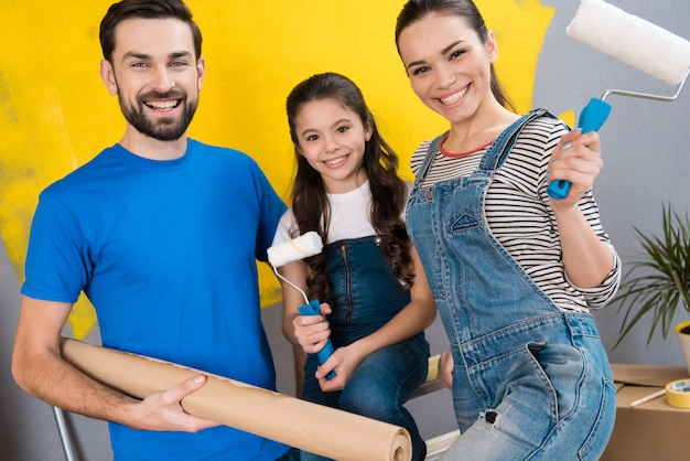 Vater, mutter und kleine tochter machen kleine renovierungsarbeiten