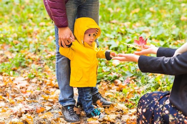 Vater, mutter und sohn gehen. baby macht erste schritte mit vaterhilfe im herbstgarten in der stadt