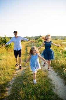 Vater, mutter und tochter haben spaß zusammen in der natur.