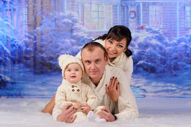 Vater, mutter und tochter liegen im schnee.