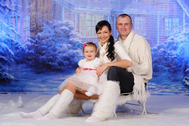 Vater, mutter und tochter sitzen auf einem schlitten im schnee.