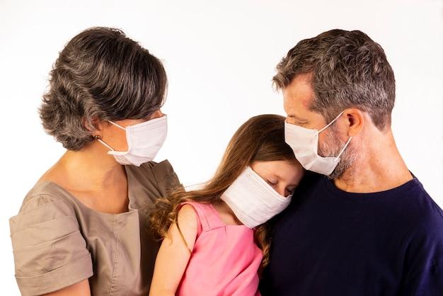 Vater, mutter und tochter tragen schutzmasken auf weißem hintergrund
