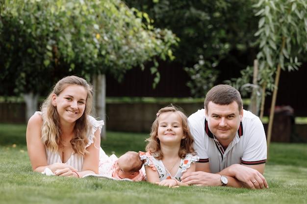 Vater, mutter und zwei kinder, baby und kleine tochter am sommertag im gras