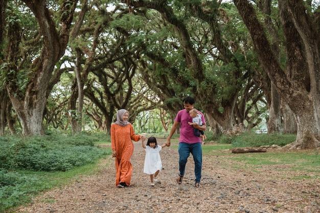 Vater, mutter und zwei kinder gehen im park spazieren